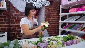 Профессиональный флорист аранжируя букет свадьбы цветка в студии флористического дизайна сток-видео