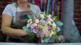 Профессиональный флорист аранжируя букет свадьбы цветка в студии флористического дизайна видеоматериал