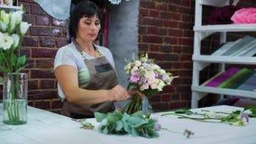 Профессиональный флорист аранжируя букет свадьбы цветка в студии флористического дизайна акции видеоматериалы