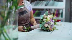 Профессиональный флорист аранжируя с букетом свадьбы цветка ленты в студии флористического дизайна сток-видео