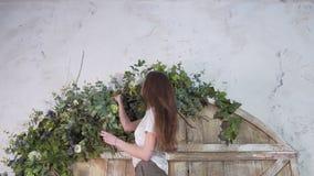 Профессиональный флорист девушки с ветвями евкалипта в ее руках украшает цветки на красивом деревянном стробе стоковые фотографии rf