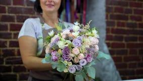 Профессиональный флорист представляя букет свадьбы цветка в студии флористического дизайна сток-видео