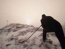 Профессиональный фотограф кладет вниз для того чтобы идти снег и принимает фото с камерой зеркала на пике Стоковое фото RF