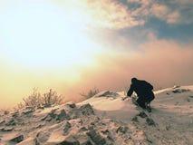 Профессиональный фотограф кладет вниз для того чтобы идти снег и принимает фото с камерой зеркала на пике Стоковая Фотография RF