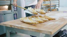 Профессиональный хлебопек принимая хлеб вне от печи в коммерчески кухне сток-видео