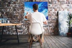 Профессиональный художник сидит на стуле перед мольбертом с холстом, paintbrush владением в руке и картиной маслом чертежа Работа стоковые фотографии rf