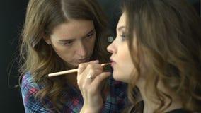 Профессиональный художник состава прикладывая яркую красную губную помаду на красивой девушке используя специальную щетку губы видеоматериал