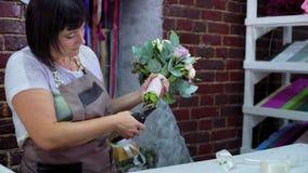Профессиональный цветок вырезывания флориста запруживает с ножницами в букете свадьбы в студии флористического дизайна сток-видео