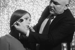 Профессиональный человек visagiste прикладывая порошок на стороне девушки с щеткой стоковое фото