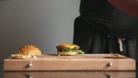 Профессиональный шеф-повар подготавливает cheeseburger с большой отбивной котлетой и салатом Подолы времени сток-видео