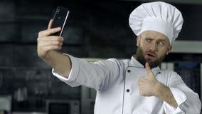 Профессиональный шеф-повар представляя на кухне Шеф-повар делая фото selfie с мобильным телефоном сток-видео