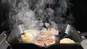 Профессиональный шеф-повар работая на кухне ресторана Картошка и мясо на гриле Белый дым над очень вкусной едой Съемка в медленно видеоматериал