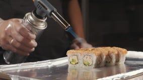 Профессиональный шеф-повар суш подготавливая крен через огонь на коммерчески кухне, конец-вверх видеоматериал