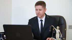 Профессиональный юрист работая на ноутбуке на таблице в офисе юриста видеоматериал
