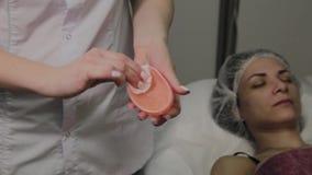 Профессиональный cosmetologist дезинфицирует аппаратуру с особенным решением Нововведения Cosmetological видеоматериал