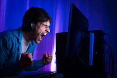 Профессиональный Gamer играя и выигрывая в видеоигре стрелка онлайн стоковая фотография rf