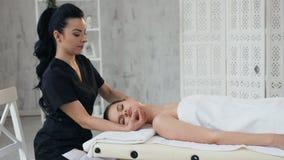 Профессиональный masseur во время процедуры по обработки с женским клиентом в стильном салоне акции видеоматериалы
