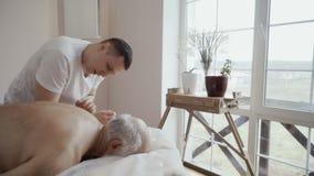 Профессиональный masseur делает массаж для старика сток-видео