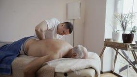 Профессиональный masseur делая массаж к старшему человеку сток-видео