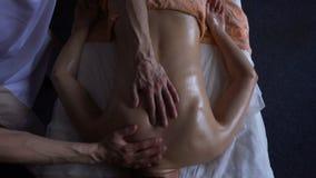 Профессиональный masseur замешивает плеча молодой женщины с теплым маслом дальше на встрече массажа взгляд сверху в ayurvedic сток-видео
