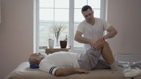 Профессиональный masseur массажирует колено ` s старика в slowmotion акции видеоматериалы