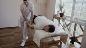 Профессиональный masseur массажирует руку молодой человек акции видеоматериалы