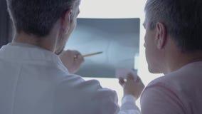 2 профессиональных доктора проверяя рентгеновский снимок, обсуждая Человек в белой робе говоря о человеческих косточках в лаборат сток-видео