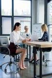 3 профессиональных коммерсантки в официальной носке работая на таблице стоковое изображение rf