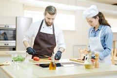 2 профессиональных шеф-повара варя в ресторане Стоковая Фотография RF