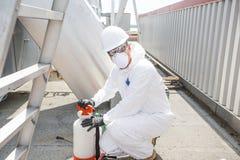 Профессионал в защитной форме, маске, перчатках в крыше для очищать стоковые фото