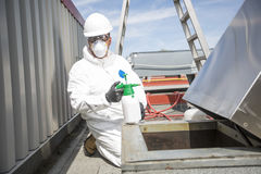 Профессионал в защитной форме, маске, перчатках в крыше для очищать стоковые изображения
