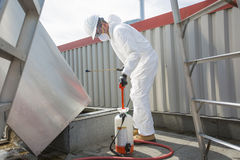 Профессионал в защитной форме, маске, перчатках в крыше для очищать стоковые фотографии rf
