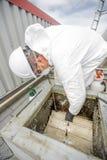 Профессионал в защитной форме, маске, перчатках в крыше для очищать стоковое фото rf