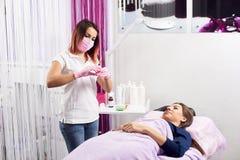 Профессионал в розовый получать маски и перчаток подготавливает шприц для того чтобы начать процедуру к молодому клиенту салона к Стоковое Фото