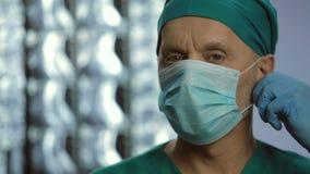 Профессионал здравоохранения принимая лицевой щиток гермошлема, усмехаясь для кулачка, доверие к клинике видеоматериал