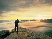 Профессионал на скале Фотограф природы принимает фото с камерой зеркала на пике утеса Мечтательный туман стоковое фото