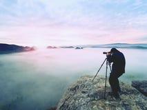 Профессионал на скале Фотограф природы принимает фото с камерой зеркала на пике утеса Мечтательный туман стоковое изображение