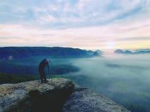 Профессионал на скале Фотограф природы принимает фото с камерой зеркала на пике утеса Мечтательный туман стоковая фотография rf