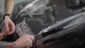 Профессионал прикладывая защитный фильм к красному автомобилю Мастер клеит защитный фильм на клобуке автомобиля акции видеоматериалы