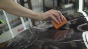 Профессионал прикладывая защитный фильм к красному автомобилю Мастер клеит защитный фильм на клобуке автомобиля сток-видео