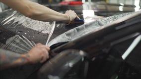 Профессионал прикладывая защитный фильм к красному автомобилю Мастер клеит защитный фильм на клобуке автомобиля стоковые изображения rf
