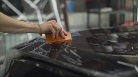 Профессионал прикладывая защитный фильм к красному автомобилю Мастер клеит защитный фильм на клобуке автомобиля стоковое фото rf