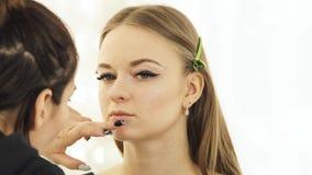 Профессионал составляет художника используя щетку косметик для вручителя ТВ женщины стороны состава Закройте вверх по visagist де сток-видео