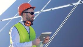 Профессионал стоит около панели солнечных батарей и работает с его планшетом акции видеоматериалы