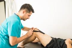 Профессионал физиотерапии прикладывая ленту KT на колене ` s спортсмена стоковая фотография rf