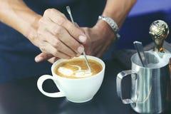Профессионал barista latte кофе делая картиной попугая i стоковая фотография