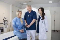 Профессионал при коллега и пациент используя компьютер перед Г-НОМ стоковые изображения
