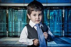 Профессионал, ребенок одел бизнесмена с руками в его связи стоковая фотография