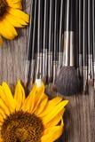 Профессионал составляет щетки рядом с красивыми полевыми цветками стоковые фото