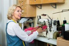 Профессионал средн-постарел портной женщины используя швейную машину стоковые фото